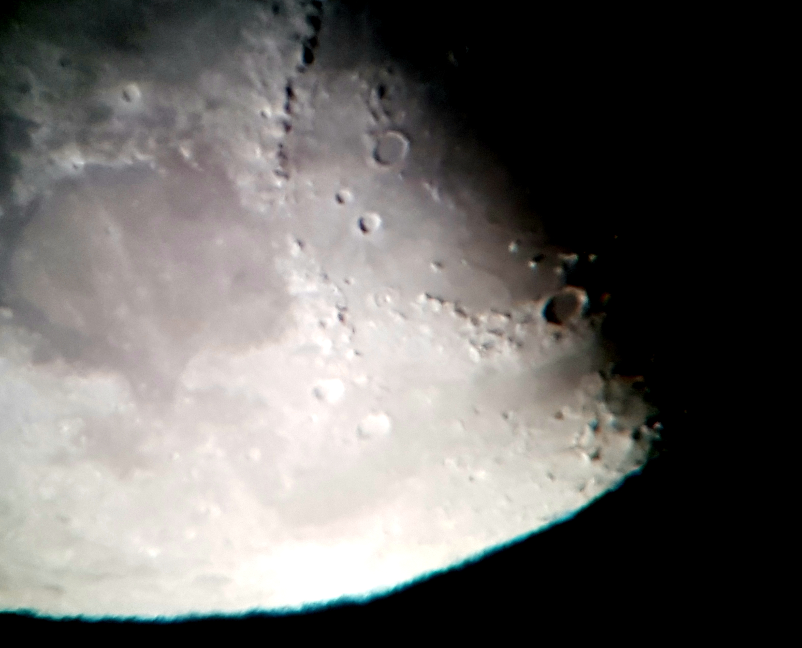 "Bill comments ""I pointed the 10"" Dobsonian at the Moon yesterday evening at 17:00 UT.  Very low in the sky and seen through the branches of a nearby tree!  Seeing atrocious and low altitude chromatic aberration, Anyway, I attempted some hand-held shots with my phone camera.  Two of them attached.."""
