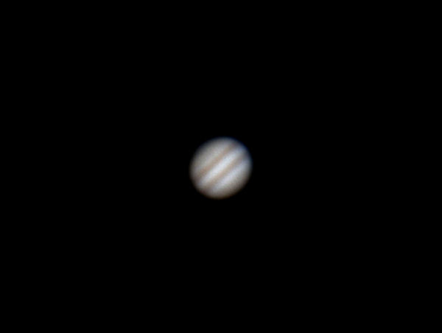 "Jupiter. By Ken Kennedy. 23rd March 2015. 21.32UT. Canon EOS-100D 1/3 second:  ISO-400. ""I went out a bit later to allow Jupiter to get a bit higher in the sky.  Tried a few shots of Jupiter and the Moon but again realised how difficult it is to focus on Jupiter.  Used x2 and x3 Barlows and I have attached the best shots.  Planets really need multiple exposures to get any detail but I'm pleased enough with what the small telescope produced with a single shot.  I think I'll revert to the 8 inch and webcam for Jupiter though""-Ken"