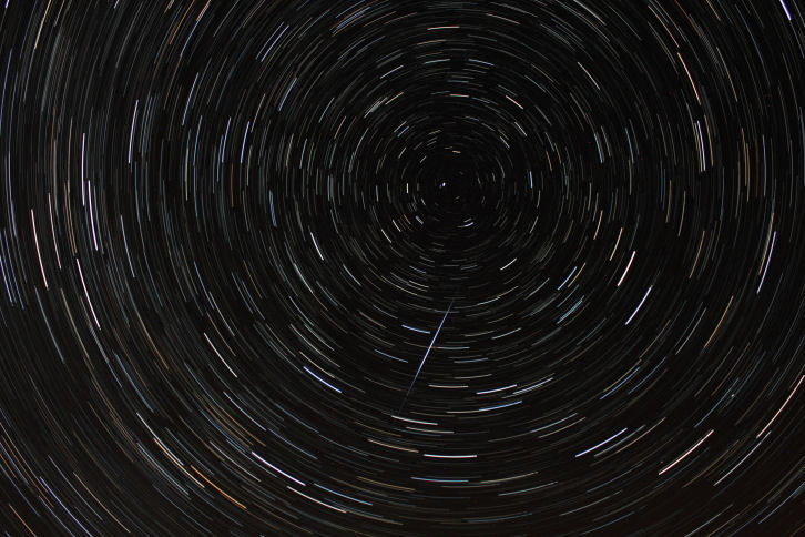 "Star trails by Pam Foster.  (No camera details) ""I've attached a star trail image that I stacked from Galloway, on the night after the aurora. There were 83 images, all of 30 seconds exposure, stacked using the Startrails software.  The probable meteor trail makes a nice addition."""